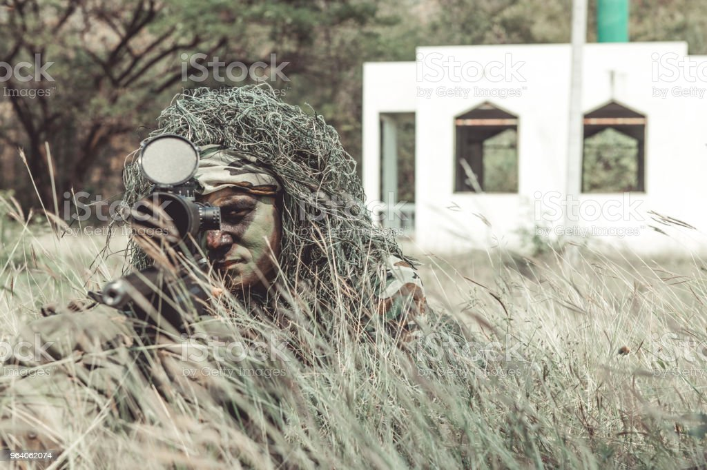 Sniper in urban combat training. Full ghillie camo suit and a high power sniper rifle. In urban combat training ground. Aiming his weapon. - Royalty-free Armed Forces Stock Photo