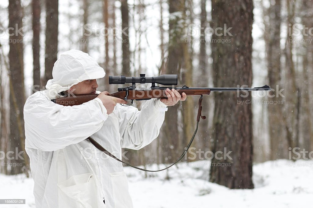 Sniper in white camouflage aiming with rifle at winter forest. royalty-free stock photo