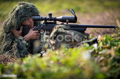 Sniper laying on the grass looking through scope at the target in deep forest.