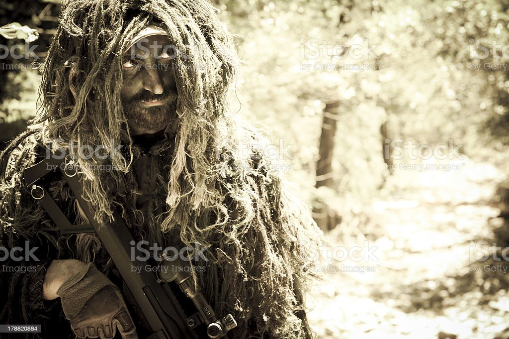 Sniper Soldier Close Up Hiding in Bush with Ghillie Suit stock photo