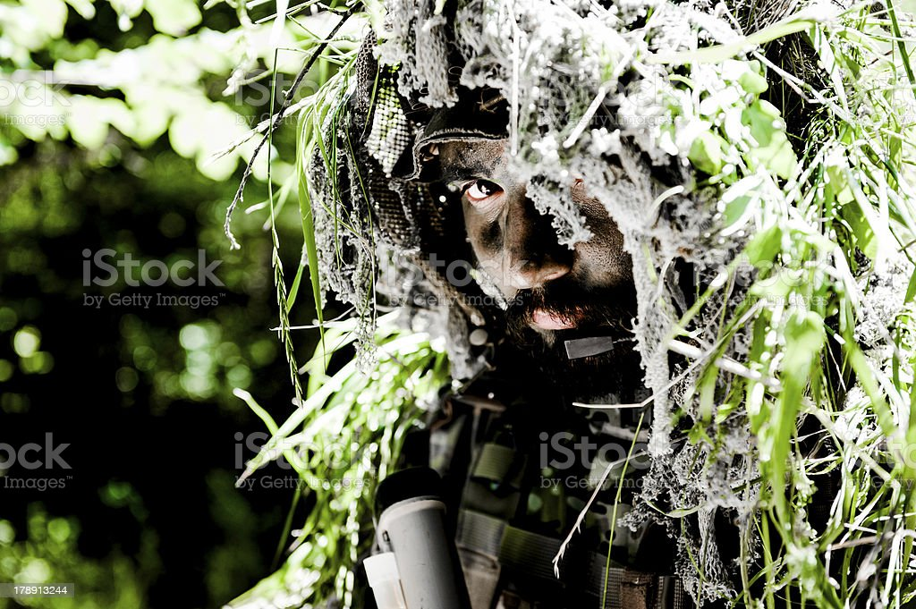 Sniper Soldier Face Close Up Hiding in Bush with Ghillie stock photo