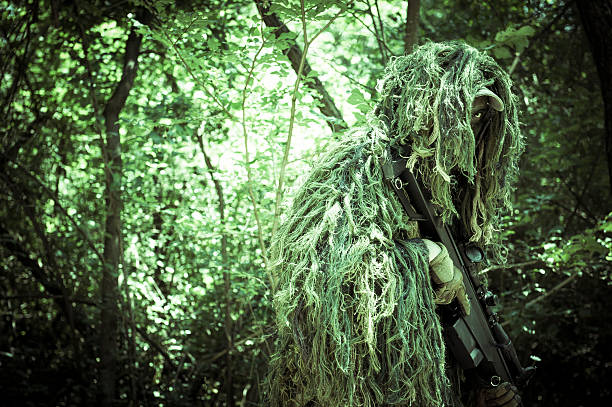 Sniper Soldier Hiding in Bush with Ghillie and Precision Rifle stock photo