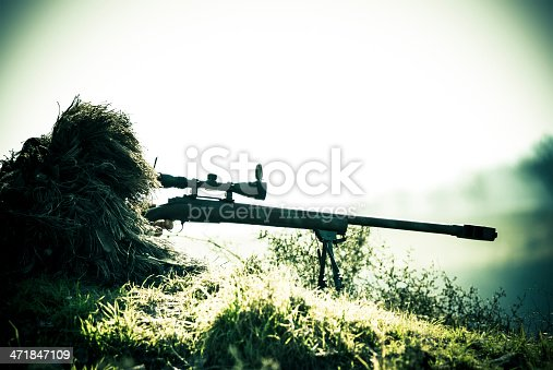 istock Sniper Soldier Silhouette in Ghillie Suit Shooting with Precision Rifle 471847109