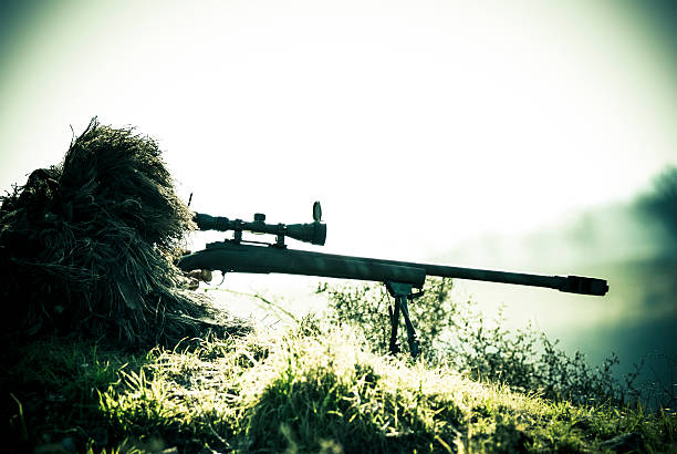 Sniper Soldier Silhouette in Ghillie Suit Shooting with Precision Rifle stock photo