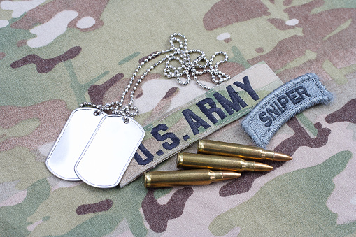 istock US ARMY sniper tab, flag patch,  with dog tag and 5.56 mm rounds and 5.56 mm rounds on camouflage uniform 1019025602