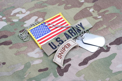 istock US ARMY sniper tab, flag patch,  with dog tag on camouflage uniform 1019025898