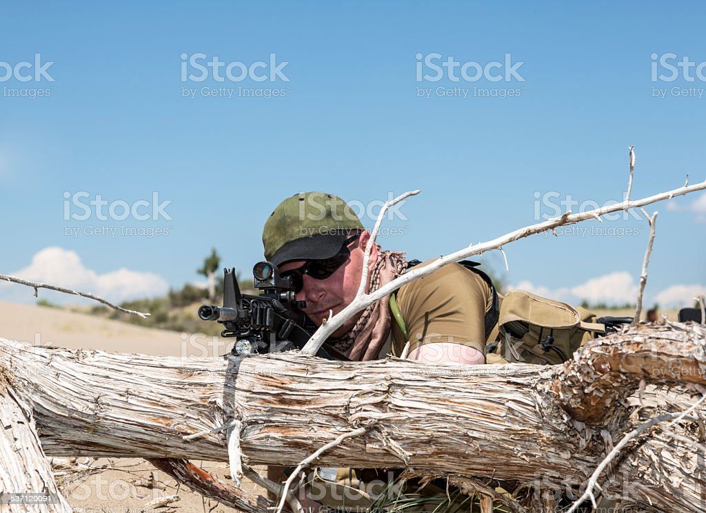 Sniper taking aim concealed behind a log stock photo