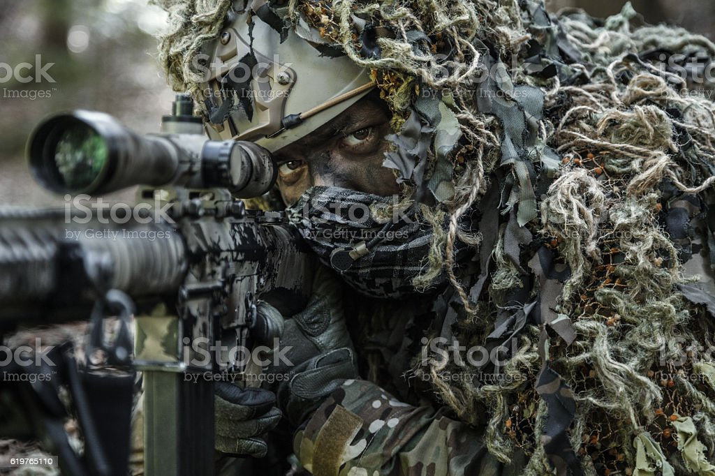 sniper wearing ghillie suit stock photo
