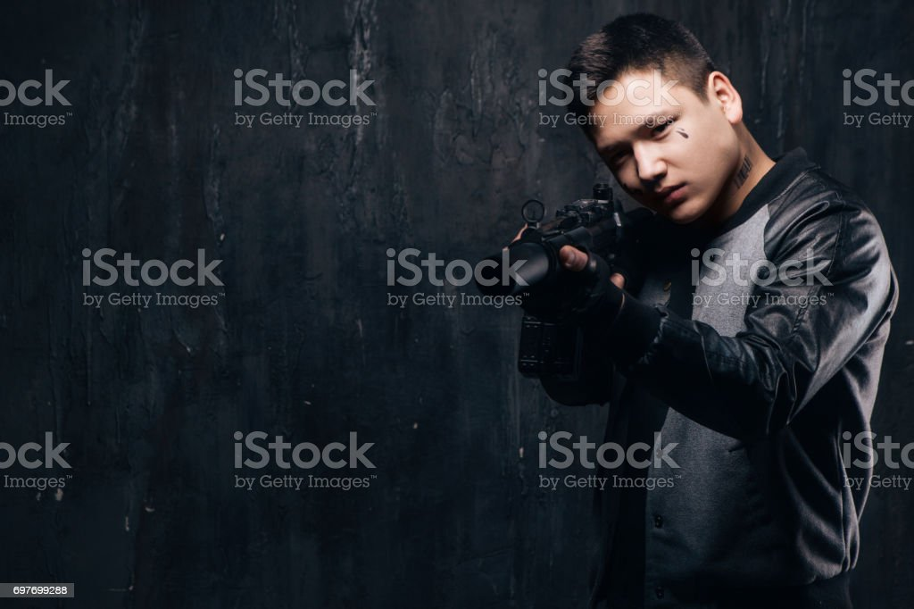 Sniper With Tear Tattoo On Face And Rifle Stock Photo