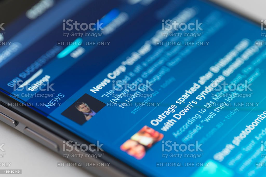 Snippets of news on iPhone running iOS 9 Melbourne, Australia - Sep 22, 2015: Snippets of news on one of the home screens of an iPhone 6 running iOS 9. This is one of the new features of iOS 9. 2015 Stock Photo