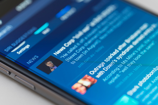 Snippets Of News On Iphone Running Ios 9 Stock Photo - Download Image Now
