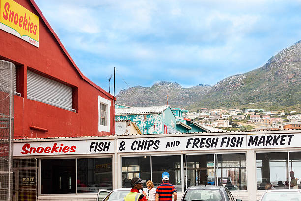 Snoekies Fish and Chips at Hout Bay harbour Hout Bay, South Africa - November, 23rd 2014: Snoekies Restaurant serving Fish and Chips at Hout Bay harbour. A popular restaurant at the harbour where people can eat fresh fish from the fishermen trawlers. Hout Bay community seen up the mountain. hout stock pictures, royalty-free photos & images