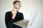 istock Snooping Computer Spy Surprised Eye in Magnifying Glass with Laptop 173040901