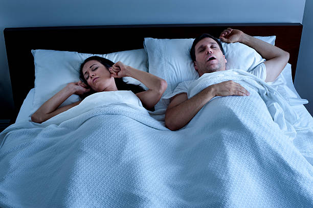 Snoring Man in Bed with Wife stock photo