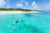 シュノーケリングで澄み切った青い水の熱帯の島、日本、沖縄