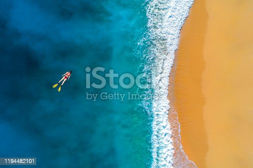 Aerial view of swimming woman in clear turquoise water. Mediterranean sea.