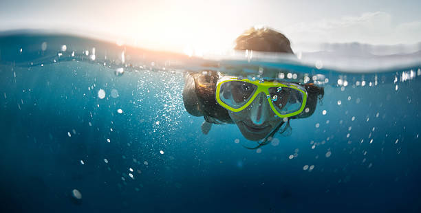 snorkeling in the sea - hair line surface stock photos and pictures