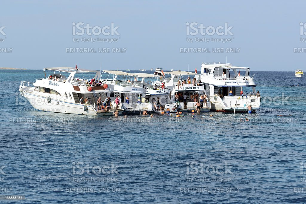 Snorkeling tourists during vacation and motor yachts on Red Sea royalty-free stock photo