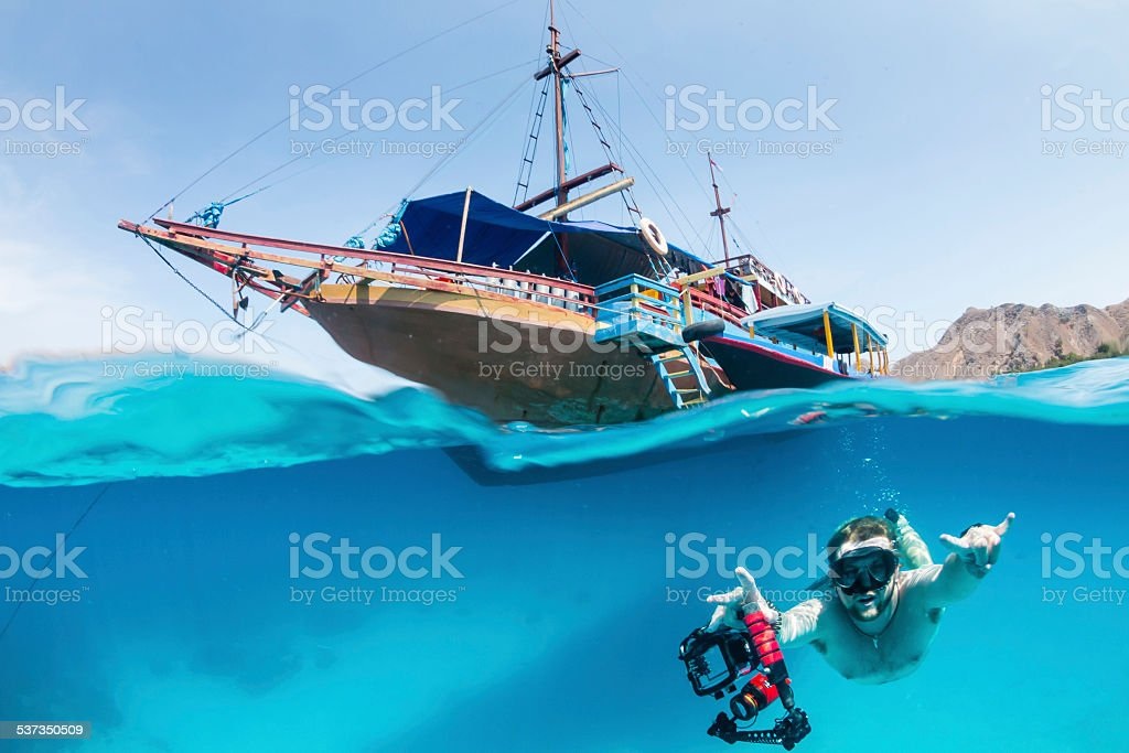 Snorkeller swims underwater close to a boat stock photo