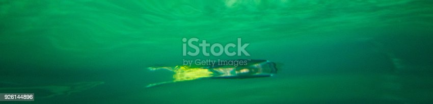 Abstract underwater reflection on the underside of the sea surface with an unrecognizable snorkeler in the background.