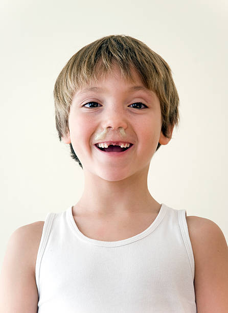 Snotty-nosed brat Portrait of a boy with missing front teeth and his nose full of mucus. mucus stock pictures, royalty-free photos & images