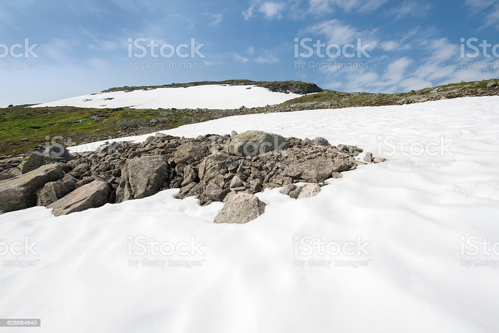 Snow and boulder hike in Norwegian summer mountains stock photo