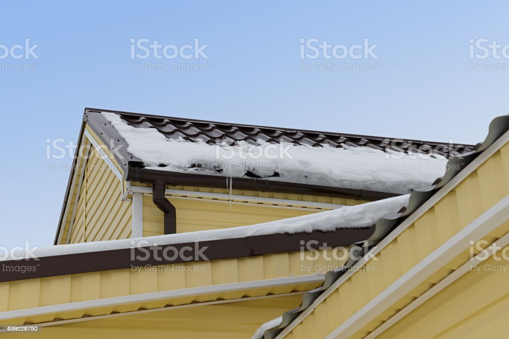snow and icicles on the roof of an apartment house stock photo