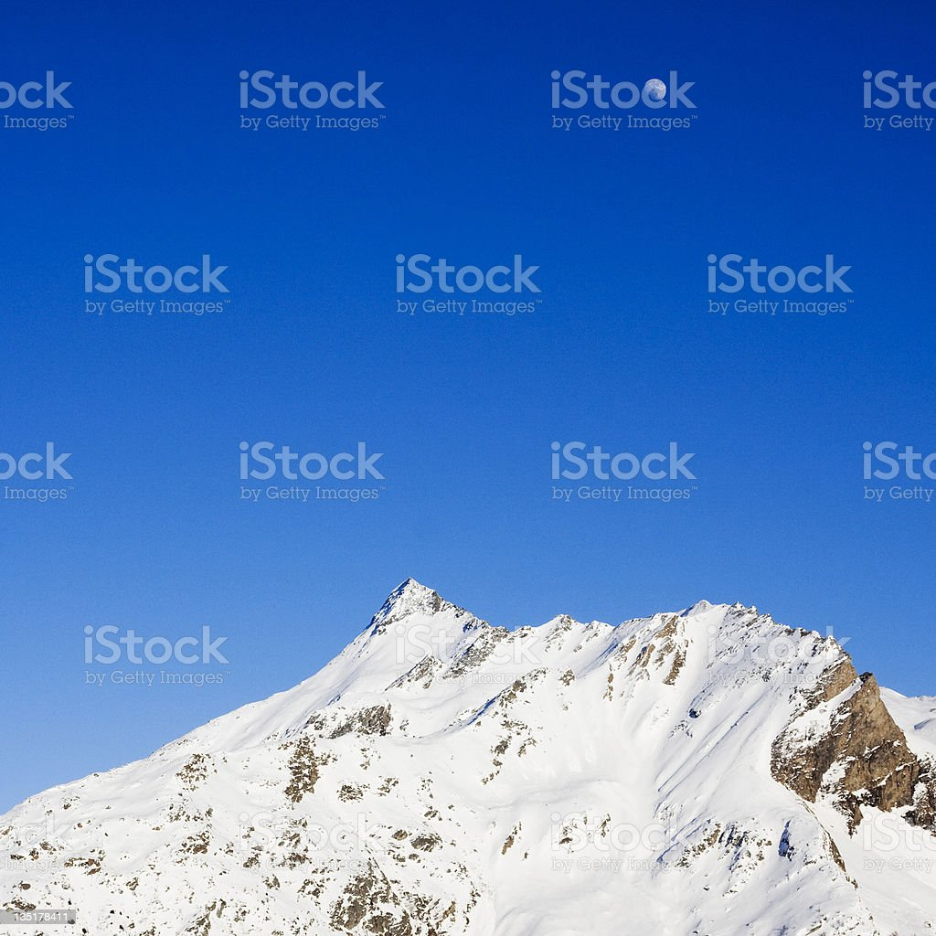 snow and moon on the mountains in winter stock photo