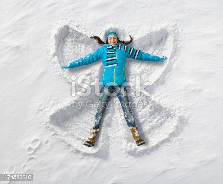Young teenage girl creating a snow angel.