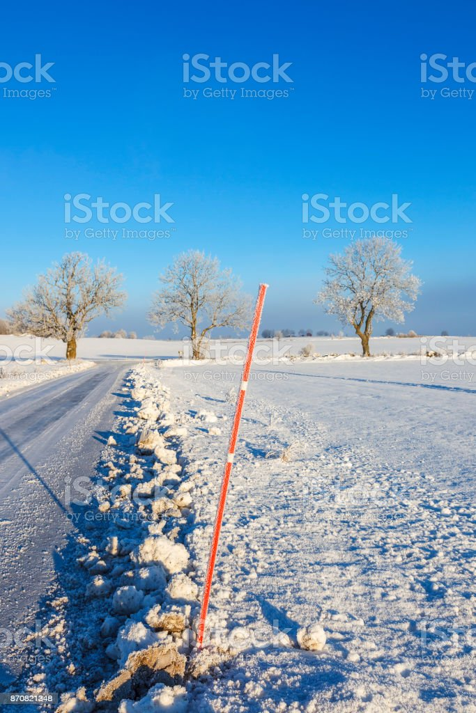 Snow bank with a stick at the road stock photo