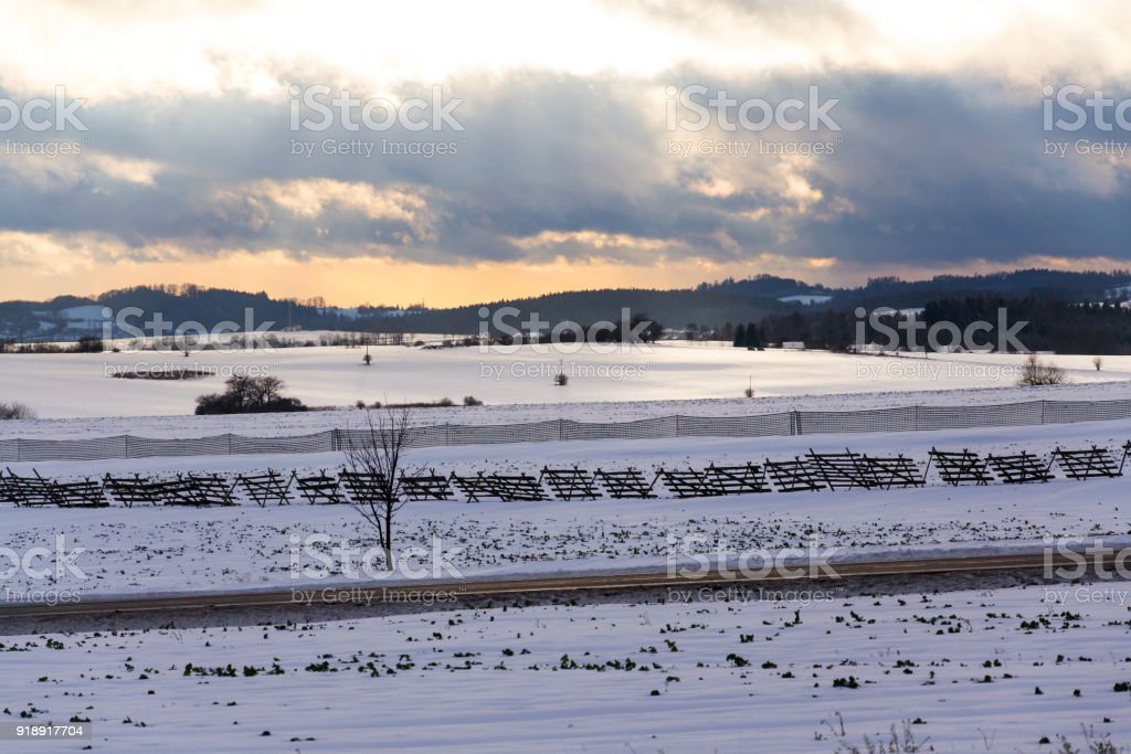 Wooden and plastic snow barriers close to road in snowy landscape...