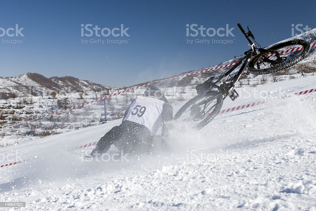 Snow biker downhill in winter mountains royalty-free stock photo