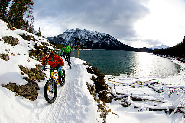 Snow Biking Couple A woman and man enjoy a winter fat bike ride in Banff National Park, Alberta, Canada. mountain biking stock pictures, royalty-free photos & images