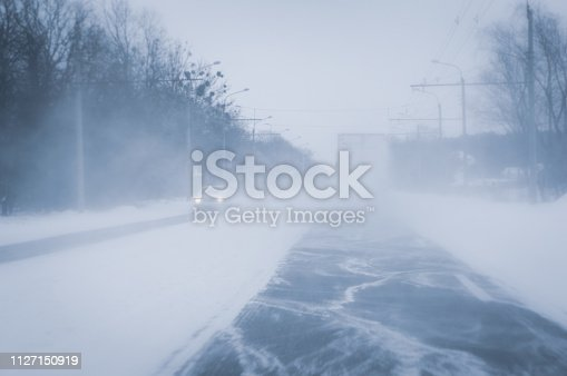 657042754 istock photo Snow blizzard on the highway road. Background with copy space. 1127150919