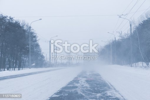 657042754 istock photo Snow blizzard on the highway road. Background with copy space. 1127150922
