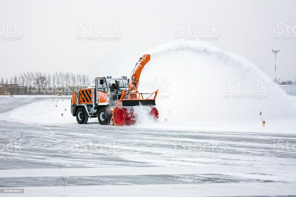 Snow blower cleans taxiway стоковое фото