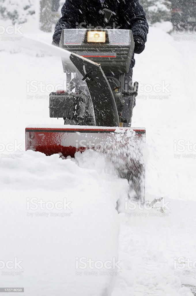 Snow blower clearing a driveway. royalty-free stock photo