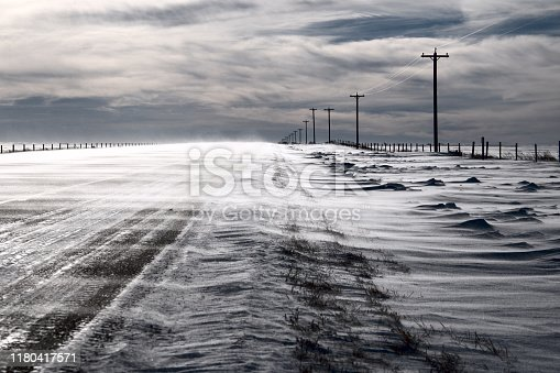 A cold and frozen winter scene of snow being blown across an asphalt highway on a cloudy overcast winter day on the Canadian Prairies.