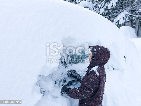 Child helping clear tons of California snow out of a driveway and off a car with a snowblower and his hands. In Truckee, California