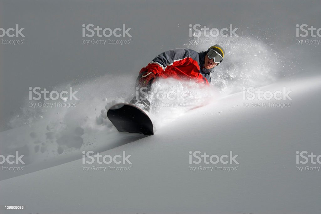 Snow boarder in bright jacket making a sharp powder turn royalty-free stock photo