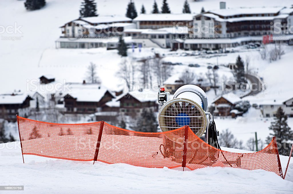 Snow cannon in the foreground of a ski area stock photo