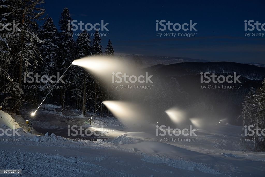 snow cannon making snow in the winter at night stock photo