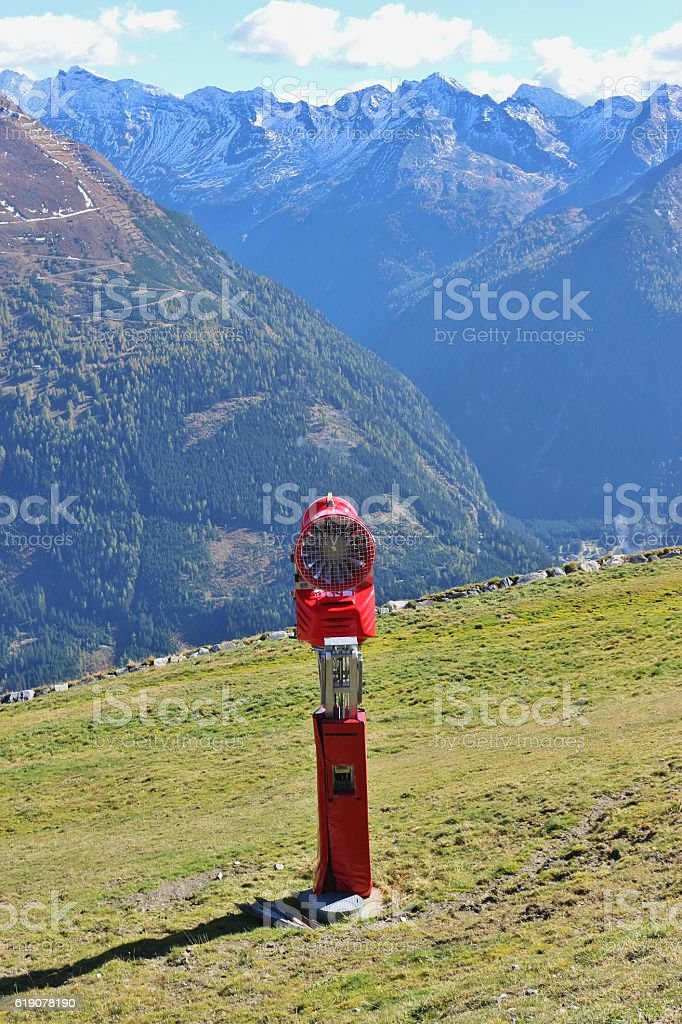 Snow cannon on green grass, Austrian alps. stock photo
