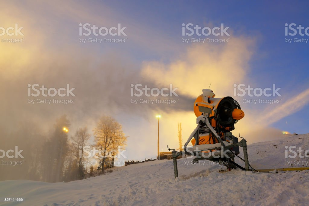 Snow cannon prepares ski slope early in the morning stock photo