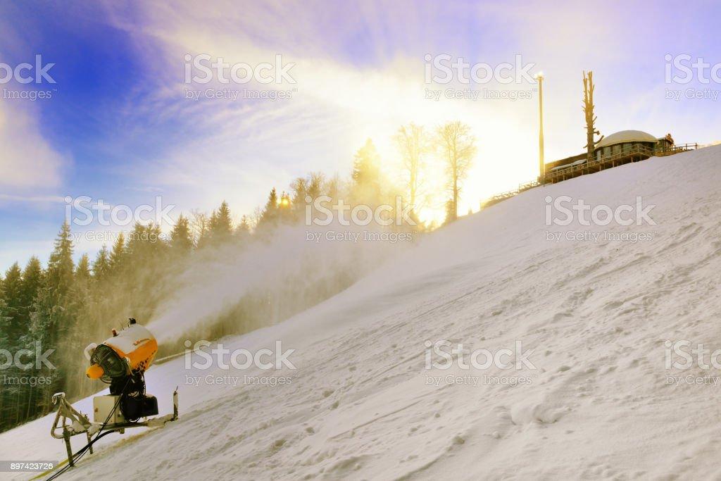 Snow cannon prepares ski slope high in the mountains stock photo
