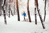 Young man with his dog jogging on winter day