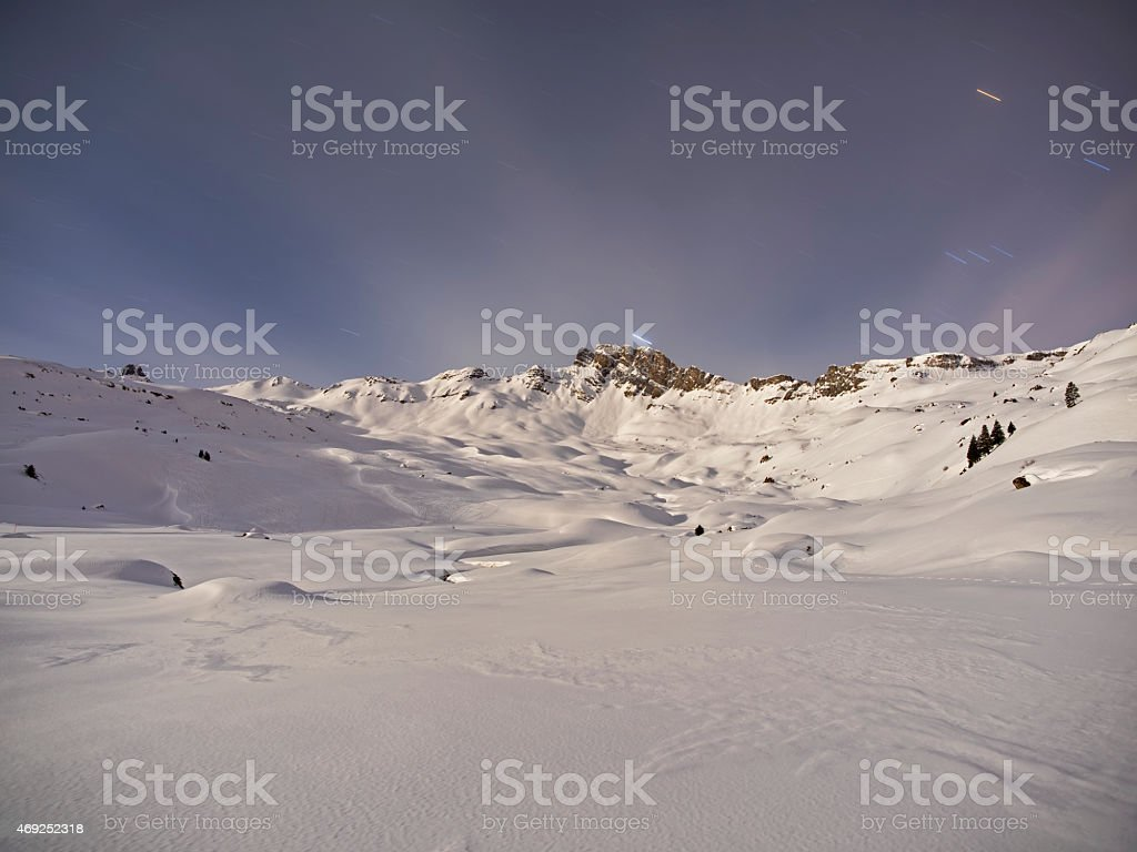Snow capped alpine landscape in the moon light stock photo