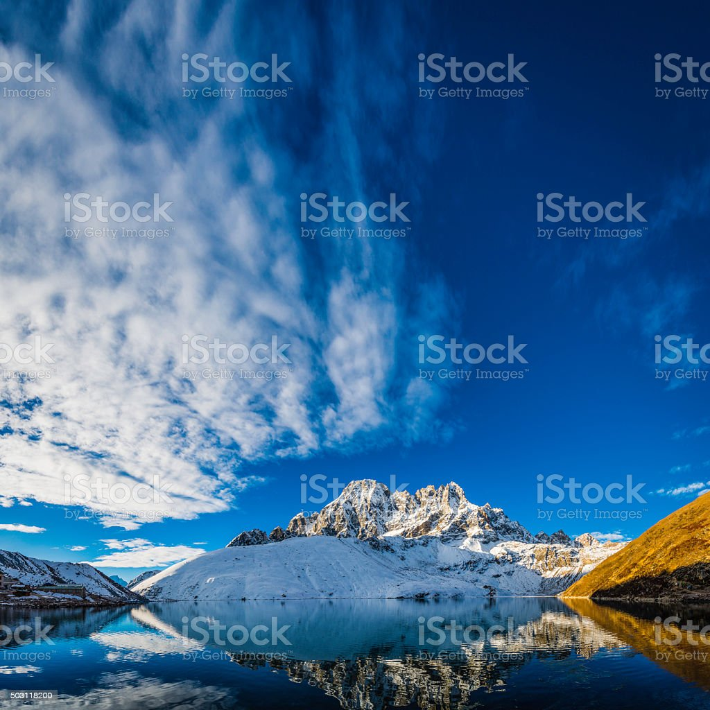 Snow capped mountain peaks reflecting in tranquil lake Himalayas Nepal stock photo