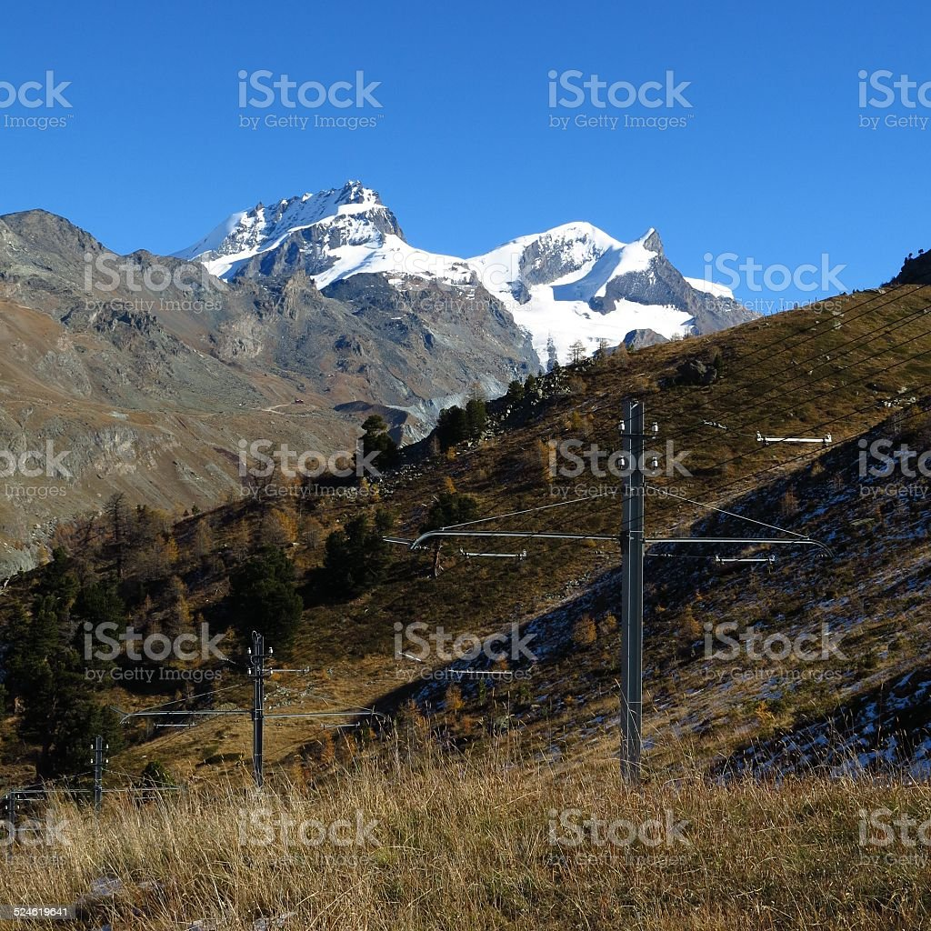Snow capped mountains and power poles of the Gornergrat train stock photo