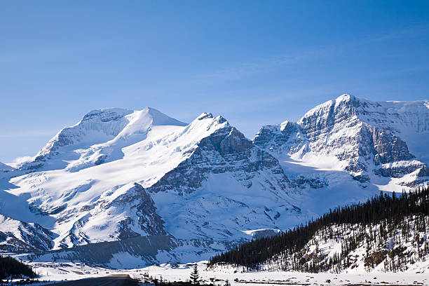 Snow capped mountains with a blue sunny day stock photo